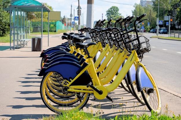 Muitas bicicletas amarelas alugadas estão paradas em um ponto de transporte público