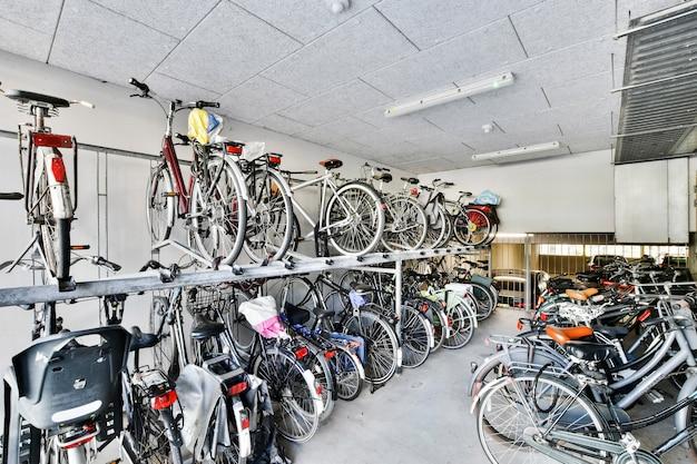 Muitas bicicletas colocadas no rack e no chão na sala de armazenamento de um prédio de apartamentos contemporâneo