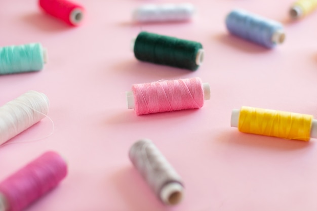 Muitas bobinas de fio de costura brilhante com um fundo rosa suave