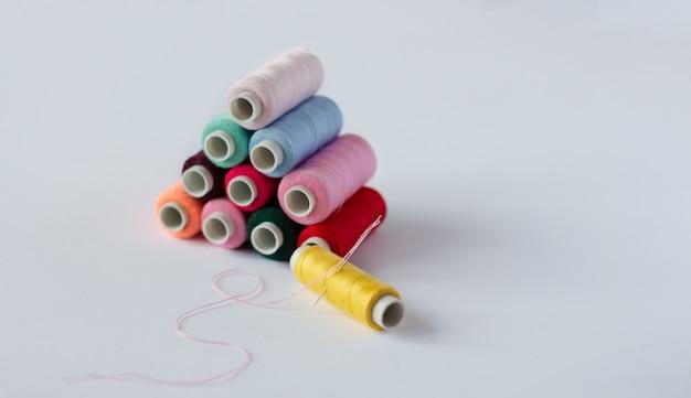 Muitas bobinas de linha de costura brilhante com uma agulha com um fundo branco isolado