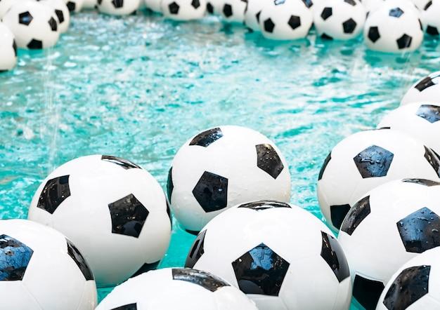 Muitas bolas de futebol preto e brancas. bolas de futebol em uma água