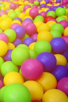 Muitas bolas plásticas coloridas no ballpit dos miúdos em um campo de jogos. fim, cima, padrão