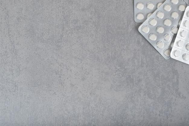 Muitas bolhas com comprimidos brancos na superfície cinza