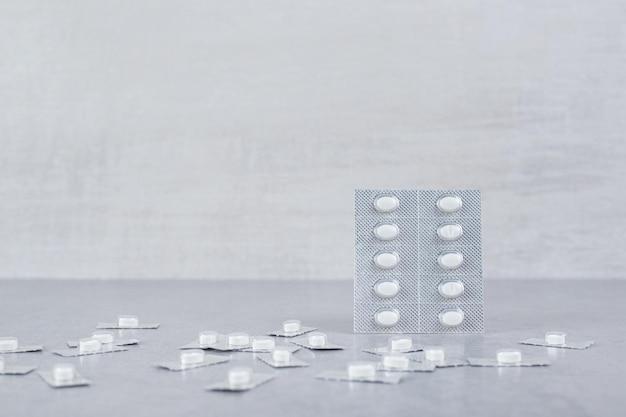 Muitas bolhas com comprimidos brancos sobre fundo cinza.
