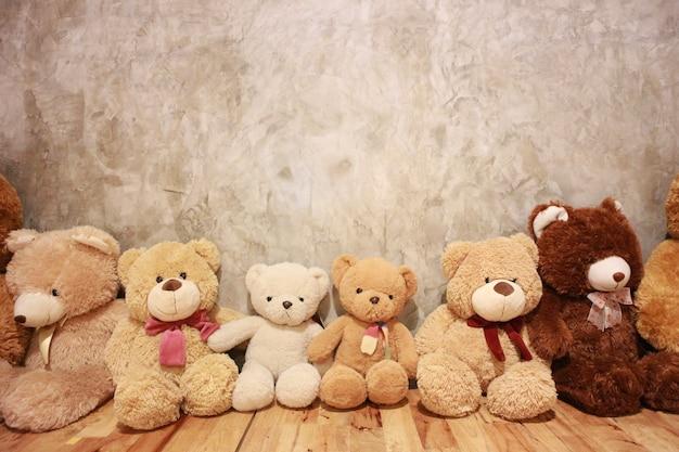 Muitas bonecas bonitos do urso estão no assoalho de madeira com parede do vintage.