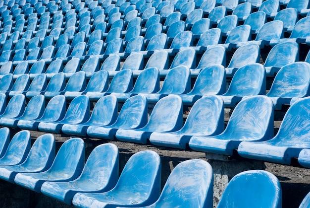 Muitas cadeiras azuis antigas em um estádio de futebol, para visitantes que precisam de substituição ou reconstrução