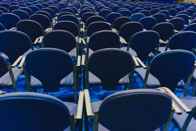 Muitas cadeiras azuis vazias da fileira em um teatro.