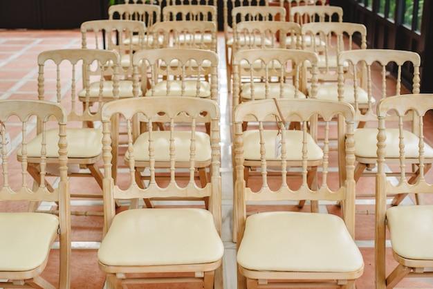 Muitas cadeiras de madeira brancas vazias alinharam para um evento retro do estilo.
