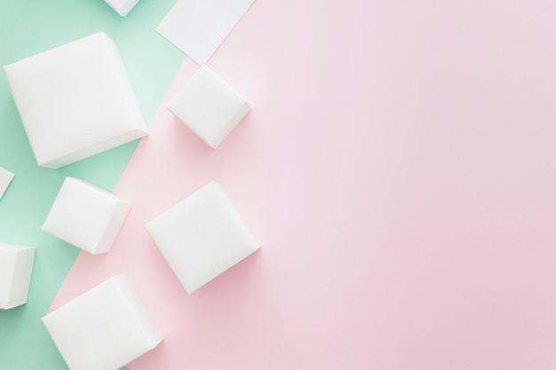 Muitas caixas brancas diferentes em pano de fundo verde e rosa