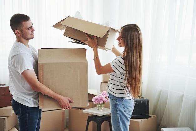Muitas caixas. casal jovem alegre em seu novo apartamento. concepção de movimento.