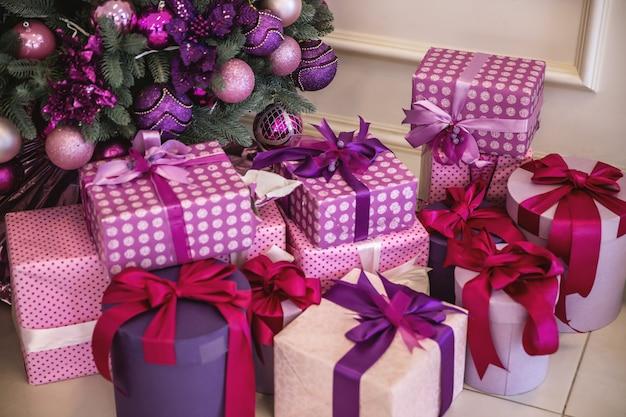 Muitas caixas coloridas com presentes de ano novo encontram-se sob a árvore de natal
