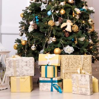 Muitas caixas com presentes dos christas perto da árvore. moldura quadrada.