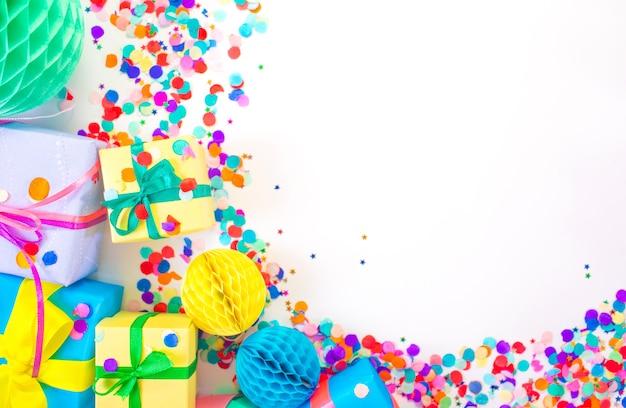 Muitas caixas de presente coloridas e confetes coloridos em um fundo branco. vista do topo