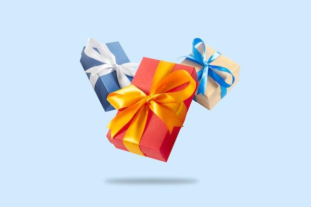 Muitas caixas de presente de voo em uma superfície azul clara. conceito de férias, presente, venda, casamento e aniversário.