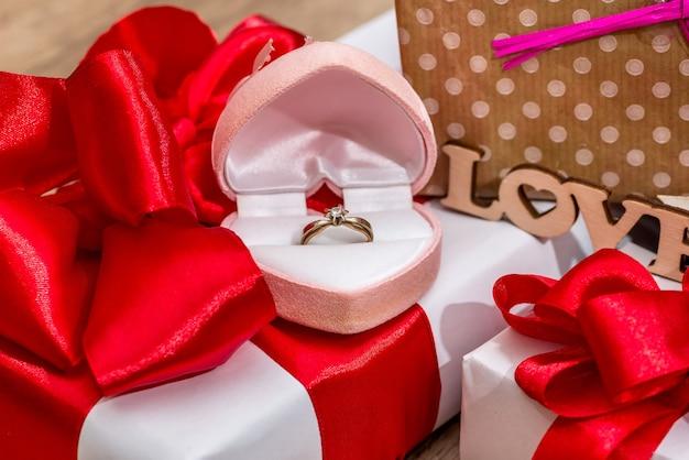 Muitas caixas de presente decoradas com laços de fita e caixa aberta com anel de ouro