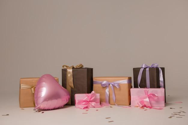 Muitas caixas de presente e um balão rosa em forma de coração em uma luz de fundo