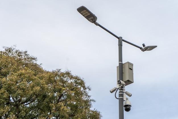 Muitas câmeras de vigilância de rua estão penduradas em um poste contra o fundo da rua