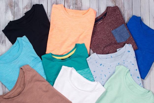 Muitas camisetas coloridas em madeira. vista superior, configuração plana