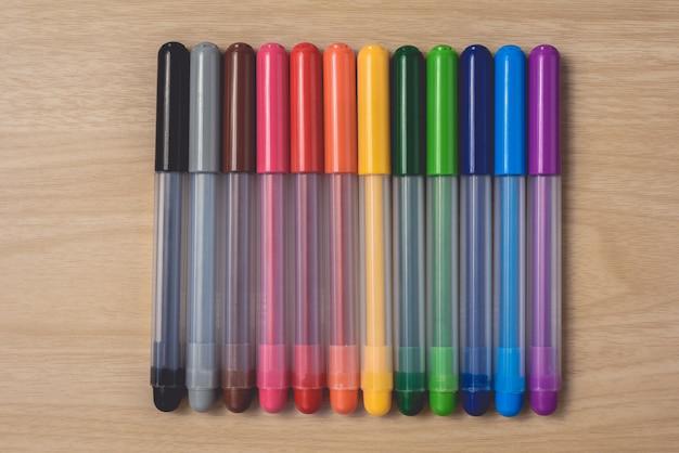 Muitas canetas coloridas na mesa de madeira marrom