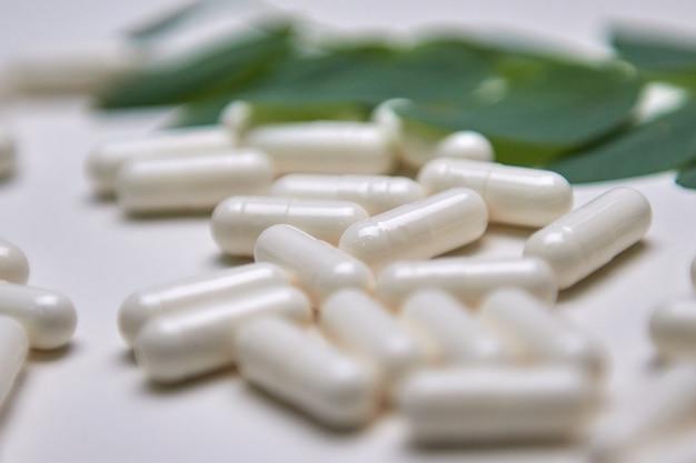 Muitas cápsulas brancas sobre um fundo colorido, suplementos e medicamentos para a saúde