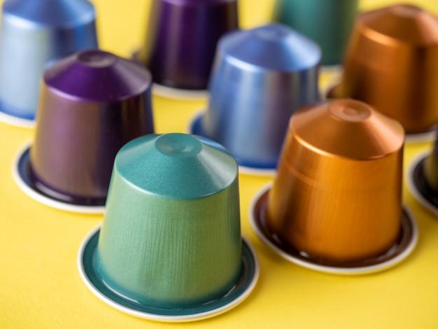 Muitas cápsulas de café de alumínio são exibidas em uma linha em um fundo amarelo. padrão alimentar