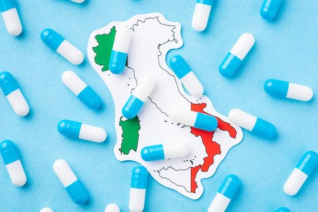 Muitas cápsulas de comprimidos médicos no topo do mapa e da bandeira da itália