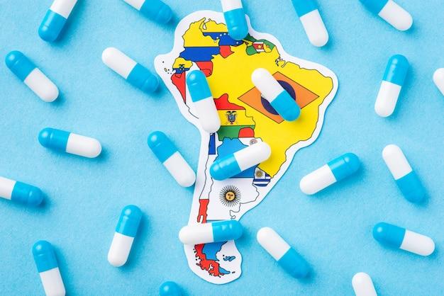 Muitas cápsulas de comprimidos médicos no topo do mapa e da bandeira do continente sul-americano