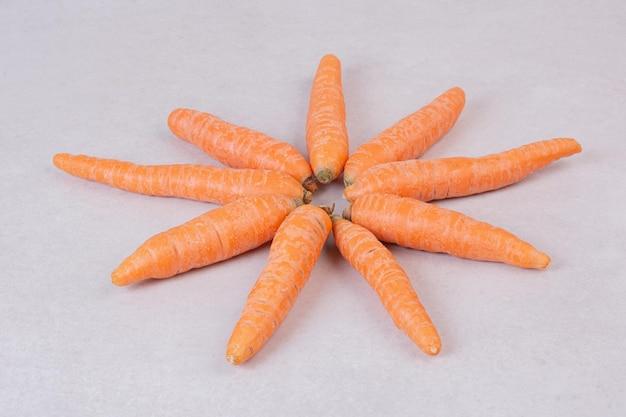 Muitas cenouras frescas na mesa branca