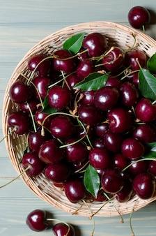 Muitas cerejas vermelhas maduras em uma cesta de vime.