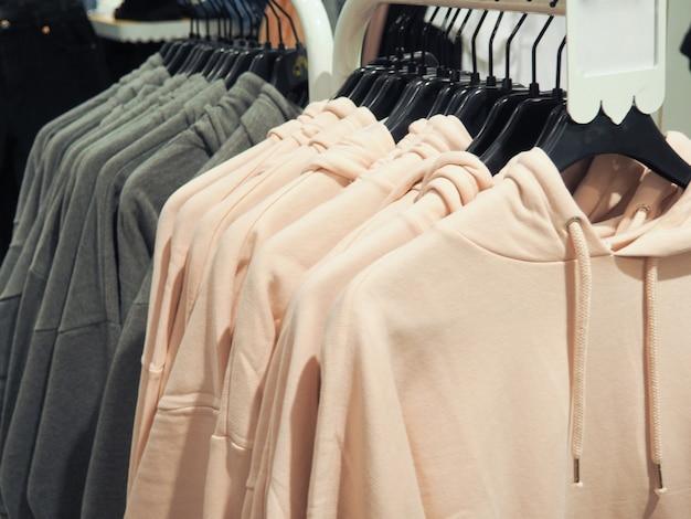 Muitas coisas coloridas penduradas no conceito de cabides da moda, compras