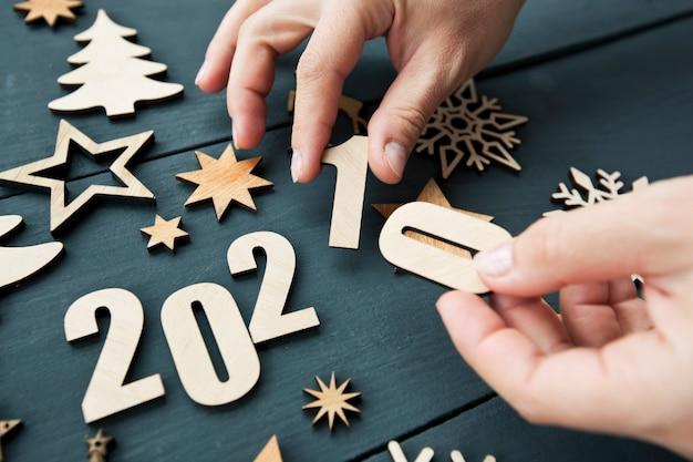 Muitas decorações de natal de madeira e a mão da mulher muda o ano