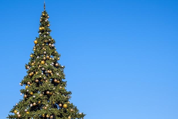 Muitas decorações e guirlandas em uma enorme árvore de natal artificial ao ar livre em um céu azul. no dia ensolarado de verão.