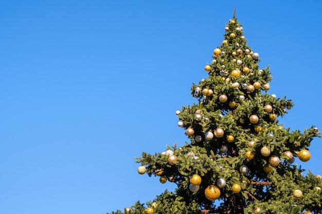 Muitas decorações e guirlandas em uma grande árvore de natal falsa ao ar livre em um céu azul. em um dia ensolarado de inverno.