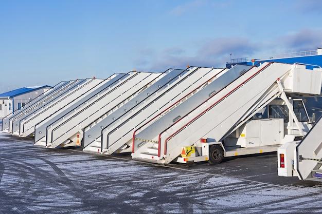 Muitas escadas de passageiros em um aeroporto de linha.
