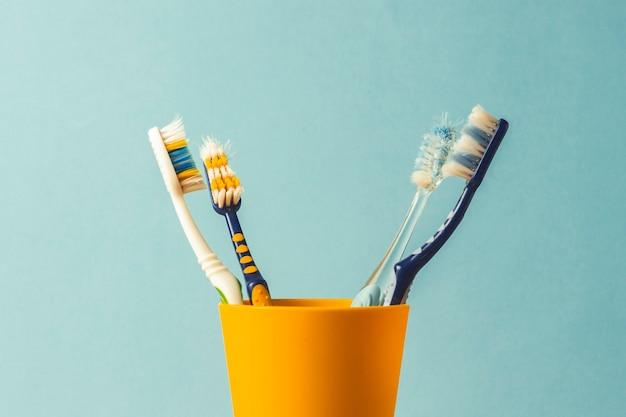 Muitas escovas de dentes em um copo de plástico sobre um fundo azul. o conceito de mudar escovas de dentes, higiene bucal, odontologia. família grande e amigável.