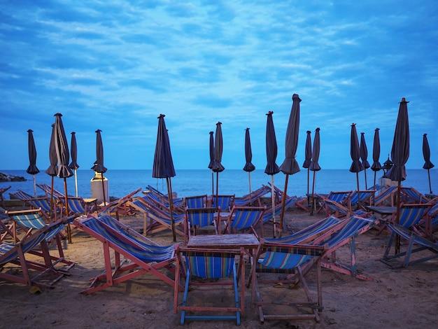 Muitas espreguiçadeiras e guarda-sóis de madeira na areia na praia do por do sol.