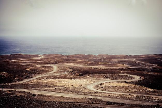 Muitas estradas são uma maneira de viajar e descobrir o deserto com o veículo preparado para viver um estilo de vida de férias diferente e incomum. praia e oceano azul no final d