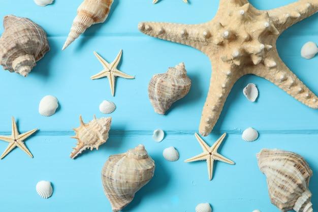 Muitas estrelas do mar e conchas do mar na cor de fundo de madeira, closeup e vista superior. conceito de férias de verão