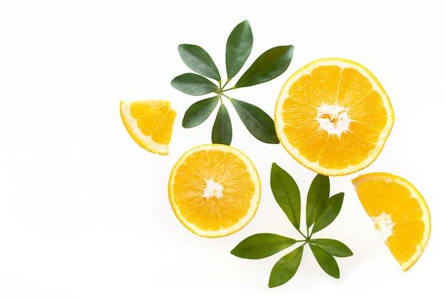 Muitas fatias de laranja frescas com folhas verdes, vista superior.