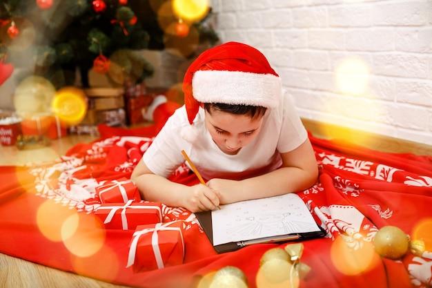 Muitas felicidades para um amigo, criança feliz, menino, escrevendo uma carta do papai noel para casa