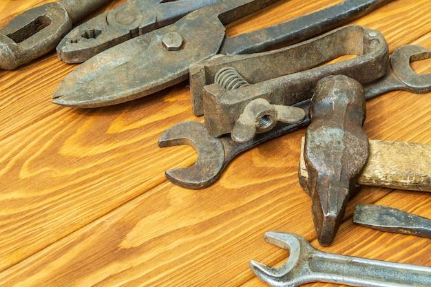 Muitas ferramentas enferrujadas empilhadas após o trabalho em um fundo de madeira vintage