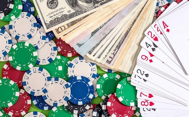 Muitas fichas de pôquer com cartas e dólares na mesa