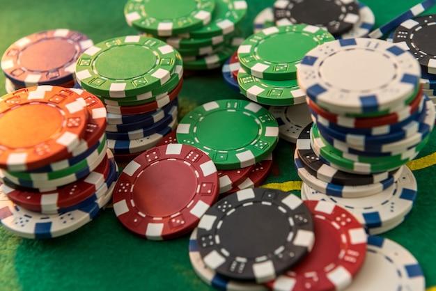 Muitas fichas de pôquer de custo diferente na mesa de jogo