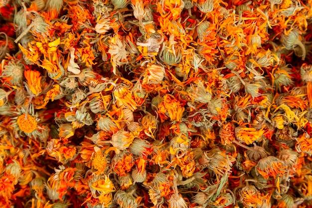 Muitas flores secas para o chá adicionar. mistura de ervas naturais antioxidantes. fundo com flores secas como um conceito de chá de ervas com ingredientes aromáticos.