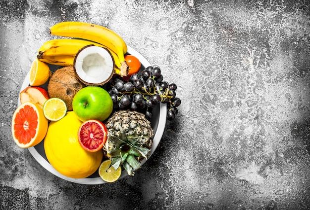 Muitas frutas diferentes em uma tigela grande. sobre fundo rústico.