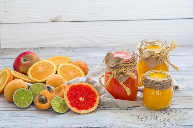 Muitas frutas frescas cortadas em um lindo fundo de madeira, bebida de frutas frescas, geléia, comida saborosa e saudável
