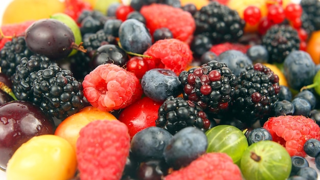 Muitas frutas frescas diferentes em um fundo branco. alimentos úteis com frutas vermelhas e vitaminas