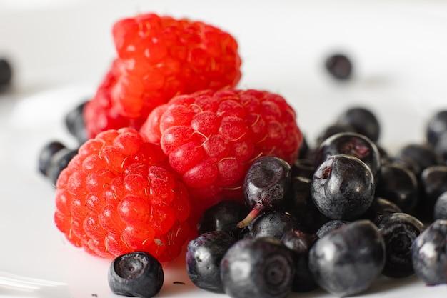 Muitas frutas suculentas e frescas de framboesa vermelha madura com amoras isoladas no fundo branco
