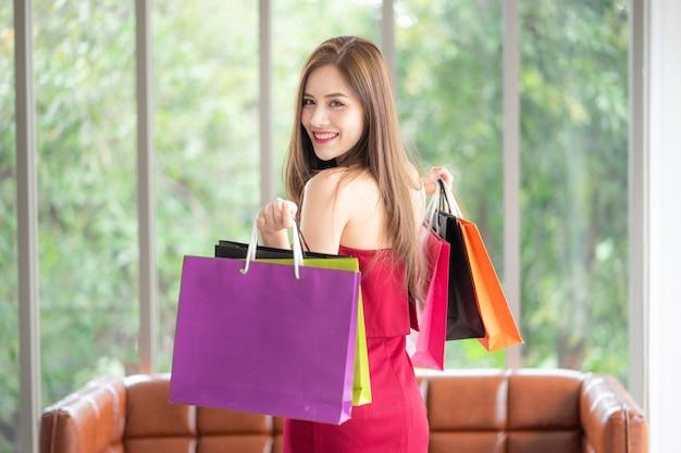 Muitas garotas são shopaholics como ela. ela é linda em vestido vermelho e segurando as compras b