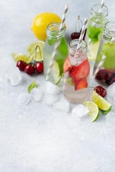Muitas garrafas com refrescante limonada de verão com limão, morango, cereja, pepino e gelo em um fundo cinza de concreto